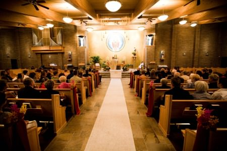 An image of the sanctuary of Little Flower Catholic Church filled with wedding guests sitting in the wooden pews listening to the priest who is standing at the altar in his white robe with the white aisle runner in the middle of the picture.