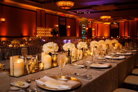 An image of a room at the Marriott at Key Center decorated for a wedding reception with long rectangular tables with gold sparkly linens and gold plates with long mirrors as centerpieces covered with candles and white floral arrangements and the perimeter of the room lit with golden orange uprights.