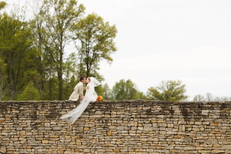 A photo taken from behind of a bride and groom sitting towards the left of the center of the picture on a tall sand colored stone wall at the Medallion Country Club, where the wall takes up the entire lower half of the photo, leaning in kissing each other with the orange and green bouquet on the wall next to the bride and green trees in the background with a white sky.