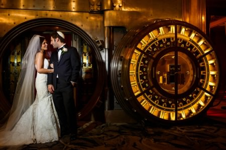 A bride in her white strapless and lacy gown with a long white veil holds tight to the arm of her groom who is in a a black tuxedo and white kippah while they look into each other's eyes smiling and standing just outside the open round-doored vault in the Metropolitan a the Nine in Cleveland, Ohio.