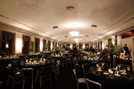 A photo taken at the end of a room at the Metropolitan Ballroom decorated for a wedding reception filled with round tables and black linens white alternating tall green and red floral arrangements with short green and red floral arrangements.
