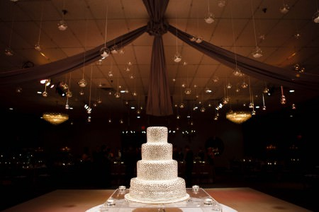 An image of a four tiered white wedding cake with round silver dots all over the it sitting on a clear square cake stand at the bottom middle of the picture with a darkened reception room in the background with clear small round globed candle holders hanging from the ceiling.