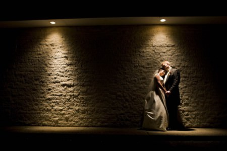 A darker image of a bride and groom holding hands where the bride is resting her head on the grooms shoulder and they are leaning up against a stone wall of Normandys in the right side of the photo taken at night where two lights are shining down and the couple is standing under the light on the right.