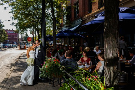 A picture of a bride and groom standing just outside an outdoor seating area of a sidewalk restaurant in Ohio City where the bride is leaning into the groom and resting her head on his shoulder while holding her bouquet in her hand and the groom is wearing dark sunglasses with his tuxedo leaning against a black railing where the tables are full of guests eating.