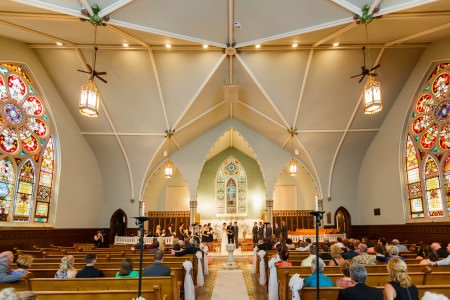 A wedding couple stand holding hands at the altar of the ornate Old Stone Chapel while the wedding guests sit in the wood pews under the extremely high ceiling with ornate stained glass windows.