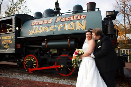 A bride in her white strapless gown leans back into the arms of her groom in his black tuxedo as they stand outside on a brick walkway in front of a green and black train engine with the words Grand Pacific Junction painted on it in Olmstead Falls, Ohio.