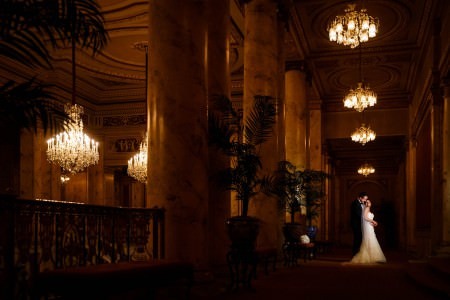 A darker picture of a bride in her white gown and long veil leaning back into her groom's arms in the lower right corner of the photo taken inside the Palace Theater with tall ornate marble pillars lining the hallway in the middle of the photo and ornate chandeliers hanging from the ceiling.