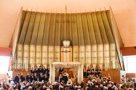 An image of a brightly lit synagogue with vaulted ceilings and oranate wooden and green and gold painted wall behind the altar, decorated with a wrought iron chuppah with white tulle and white and pink flowers, a large wedding party dressed in black on the two-tiered steps of the altar, and all pews full of wedding guests.