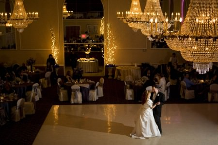 A bird's eye view of a bride and groom dancing on the shiny cream colored floor in the lower right corner while orange sparkly crystal chandeliers hang from the ceiling in the upper right corner and round tables in white linen and dark tulle bows tied around the chairs line the dance floor that's all lit in a golden color at Pazzo's Grand Ballroom in Parma, Oh.