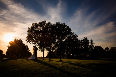 A stunning sunset image of a bride and groom standing on a grassy hill under a tree with the golden and blue sky as a backdrop at the Portage Country Club in Akron, Ohio.