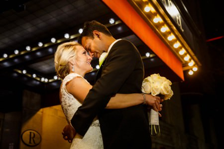 A picture of a bride in her lacy gown embracing her groom in his dark tuxedo while holding her white rose bouquet at his back and foreheads touching directly under the yellow cafe lights of the Renaissance Hotel sign and awning in Public Square at nighttime in Cleveland, Ohio.