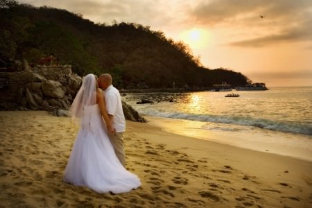 A picture of a bride and groom walking away on a Puerto Vallarta beach with the sun setting behind the rocky coastline.