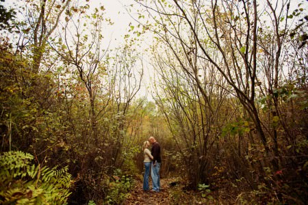 A picture of an engaged couple standing outside on an overcast fall day in the middle of the lower half of the photo on a path of fallen brown leaves wearing jeans and brown shirts surrounded by tall brown skinny tree trunks with sparse green leaves at Quail Hollow State Park in Ohio.