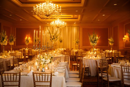 A photo of a room set for a wedding reception with both round and rectangle shaped tables, gold chairs, white linens and clear glassware lining the tables as well as tall ornate white and green floral arrangements and tall silver candelabras, and the far wall has some white drapes in the middle where the whole room glows in a golden yellow and orange hue from the lighting.