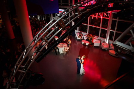 A bride and groom slow dance in the lower left corner of the photo on a floor lit with red lights and an arched silver tress running from the lower left corner to the upper right corner and guests seated at round tables in the upper left corner with tall pillars running from floor to ceiling at the Rock and Roll Hall of Fame.