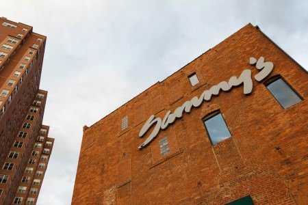 A photo of the outside of a brick building which is in the middle and right of the photo looking upward from the ground toward the grey and cloudy sky and the cursive grey lettering that spells Sammy's on the upper part of the building with another brick building fill of rectangular windows on the right side of the photo.