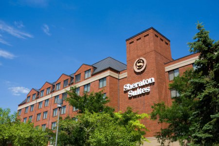 A picture taken of the outside of the red brick Sheraton Suites hotel in Cuyahoga Falls where the building is in the center of the photo with the name in white letters and logo mounted above the letter to the front of the building and green trees in the lower half of the photo all set in front of a bright blue sky.