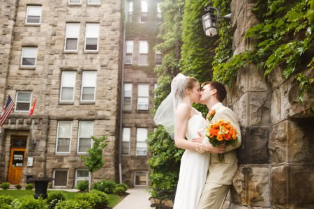 A picture of a bride and groom who are standing in the right of the photo where the bride is wearing a white gown with a veil and holding an orange and green bouquet and leaning into the groom for a kiss as he is wearing a tan suit and leaning with his back against a tall stone building that turns in an angle to take up the back of the photo with green vines growing on the building.