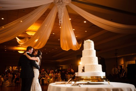 A bride and groom stand in the lower left corner slow dancing in each other's arms with the white 4 tiered wedding cake sitting on a round table in the right forefront of the photo all under an amber colored draped ceiling.