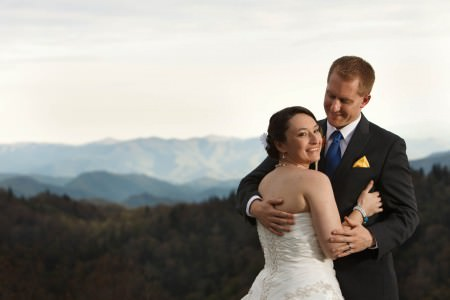 A picture of a bride standing with her back to the camera in the right side of the photo with a white strapless gown that laces up holding her groom who is facing the camera while looking down at the brides face in his black tuxedo with blue tie and yellow handkerchief tucked in the pocket with blurred out image of the pine trees behind them that move up towards the center of the photo leading to the Smoky Mountains all under a bight white sky.