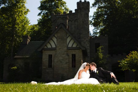 A photo taken outside on a beautiful sunny day from the ground level through grass of a bride and groom sitting and leaning forehead to forehead while the sun shines directly on them and the bride's gown and veil is spread out toward the left of the photo and Squire's Castle with it's stone and Tudor style building is in the shadows in the background of the photo with dark trees surrounding the building.