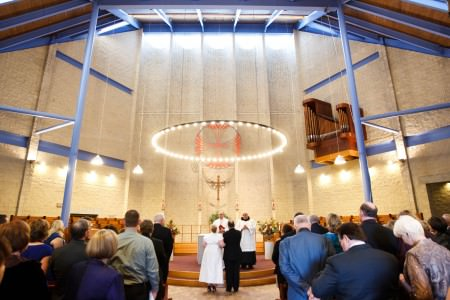 An image of a bride and groom standing at the altar of a vaulted sanctuary at St. Andrew Abby with bright blue beams, white brick walls, and a unique chandelier with plain white bulbs placed in a large round circle that is hung directly above the altar.