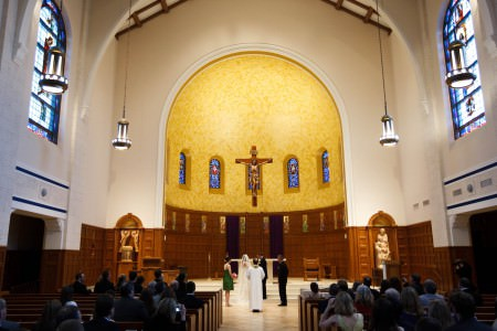 A bride and groom stand in the middle bottom portion of the photo at the altar of St. Christopher with the maid of honor in green to the left and the best man in a black to the right and the priest stands with his back to the camera while the guests are seated in their pews watching in the incredibly high vaulted ceiling with a rounded arched shaped altar area with with blue stained glass windows set in a golden painted wall and a statue of Jesus on the cross hung in the middle of that wall.