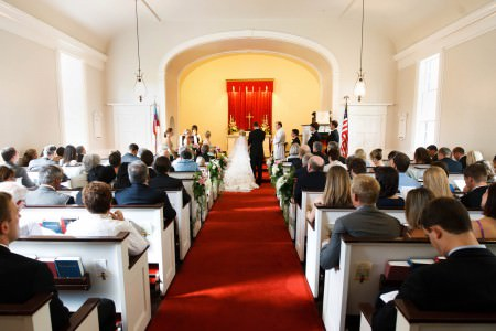 A picture taken down the red carpeted center aisle of a bride and groom standing at the altar with the priest and the wedding party with stark white walls of the sanctuary of St. Christopher's on the River with stark white walls, white and dark wooden pews full of guests watching the wedding ceremony.