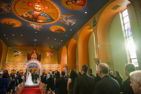 A picture of a bride and groom standing at the altar in the lower left corner of the photo inside the very colorfully painted sanctuary of St. Constantine Green Orthodox Church with a dark blue painted ceiling that has dark gold circles with Jesus painted in the center circle and saints painted in the others as well as orange arches on the right up against a green painted wall with tall narrow stained glass windows set inside each arch.