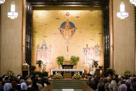 A picture of wedding guest sitting in the pews in the lower portion of the photo in the sanctuary inside St. Gregory The Great church where the wall behind the altar is frames with marble pillars a painting with Jesus on the cross in the very upper middle and saints painted on each lower side all set on a shiny gold wall.