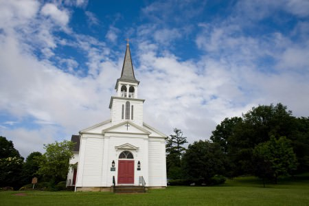 A photo of the outside of a tiny white church with a red door and a steeple is in the left center sitting on a flat green lawn with green trees surrounding the church all under a blue sky with white puffy clouds.