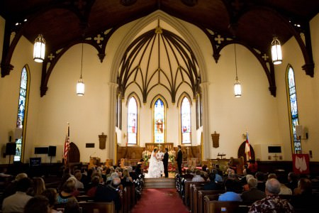 An image of a bride and groom standing on the altar of the lower center of the photo at St. James Episcopal church with the cream colored walls and dark wooden framed arched windows behind them with stained glass and guests on either side of the aisle sitting in dark wooden pews watching the wedding ceremony.