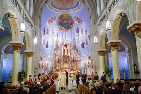 A photo of a bride and groom standing facing at the altar in the lower center of the photo with the bridesmaids in maroon dresses to the left and the groomsmen in black tuxedos to the right and the wedding guests seated in the wooden pews on either side of the center aisle inside the super vaulted and arched ceiling of the brightly blue painted St. John Cantius church with images of clouds, saints, and angels painted on the walls.