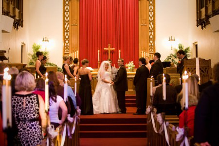 A picture of a bride and groom standing in the center of the photo down the aisle on a red carpeted altar holding hands and turning their heads toward the guests who are standing in the wooden pews with white ribbons and tall candles lit at St. John's of Dover.