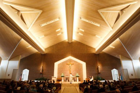 A photo taken down the center aisle of St. Joseph Parish of a bride and groom seated on the platform in the lower right of the photo facing the guests who are seated in the wooden pews on either side of the center and the priest in his white robe standing in the middle on the platform under a vaulted wooden ceiling where bright white lights are shining on the ceiling from the cross beams making the whole room bright.