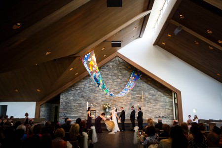 A photo of a bride and groom standing and holding hands at the altar which is in the center lower half of the image and the maid of honor is adjusted the bottom of the bride's gown inside St. Noel Church where the wall behind the altar is plain white on the far right and the rest made of small grey stonework with a triangular shape framed with a wooden beam above it and a wooden slated ceiling