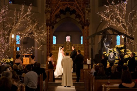 A picture looking down the center aisle of a bride and groom standing at the altar of St. Patrick's Church in Youngstown, Ohio where they are facing each other and holding hands while the priest stands in front of them in his robe with his back to the camera and the best man to the right of the priest and the maid of honor to the left while the wedding guests stand up from the wooden pews watching with bare branched trees decorated in white twinkle lights are on either side of the photo.