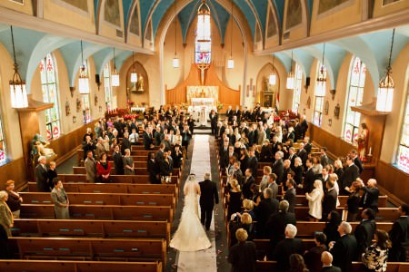 A picture taken from the balcony inside St. Paul Croatian Church looking at the back of the bride being walked down the aisle by her dad in the lower center of the photo on a white aisle runner covered with flower petals and the wedding guests standing at the wooden pews on either side and the church walls painted in a golden yellow and light teal color with arched walls with stained glass windows.
