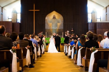 An image of a bride and groom standing with their backs to the camera holding hands at the altar of St. Paul Lutheran Church where they are fully in focus in the center of the photo standing on golden carpet and the back dark wooden wall with a large painted picture of Jesus is out of focus and the guests are seated in wooden pews lined with white tulle.