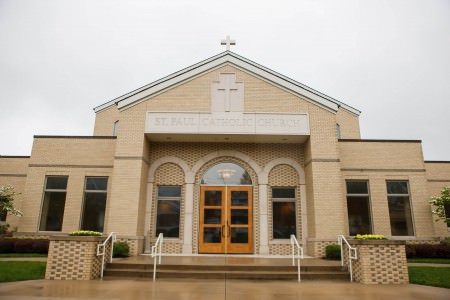 An outdoor picture of the front of the St. Paul Catholic Parish with light wooden double doors and a tan building with a white cross at the peak of the roof.