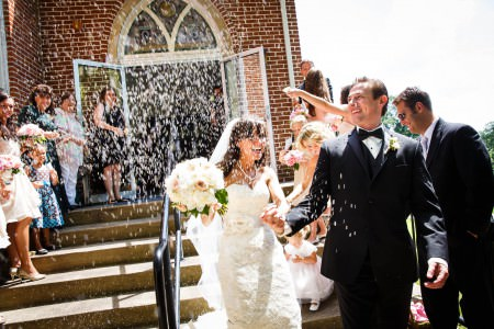 A bride and groom holding hands and smiling while exiting down the cement steps of St. Peter's Parish brick building on a bright sunny day while the wedding guests toss bird seed at them.
