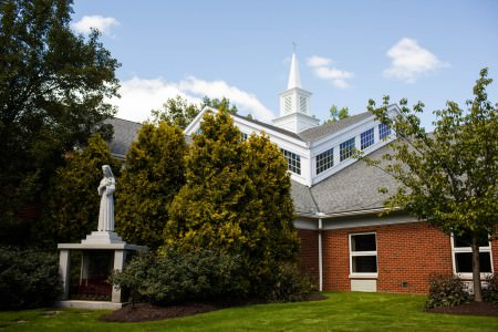 An image of St. Rita church taken from the green grass facing the inside corner of the brick building which has a grey slanted roof with a row of white windows on top and a white steeple and large green shrubs and trees are in front of the building all under a blue sky with a few white puffy clouds.