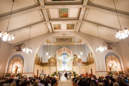 An image of a bride and groom kneeling at the altar of St. Rocco church with their guests seated in the wooden pews and the focal point of the photo is the tall vaulted white painted ceiling divided into square sections with a few small paintings and an arched wall above the altar with more scenery painted along the wall behind the altar all done in light blues, greens, and yellows.