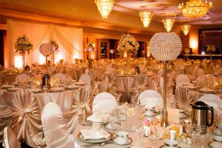 A picture of a room at St. Vladimir's Grand Hall decorated for a wedding reception with round tables and chairs draped in champagne colored satin linens, white and gold tableware, and tall thin brass candle holder with a crystal globe at the top on the table in the right lower corner.