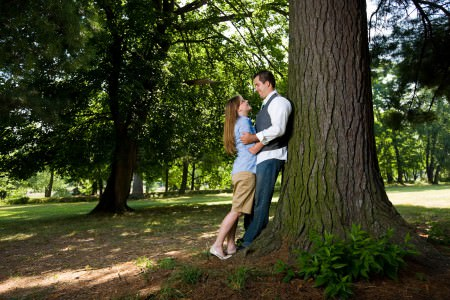 An engaged couple wearing blue and white look at each other while hugging and leaning up against the trunk of a large tree with green moss growing on the bark and more trees in the background at the Stadium Park in Canton, OH.