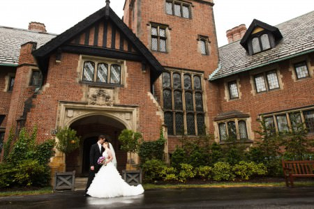An image of a bride in her white gown holding a purple and white bouquet while embracing the groom in his black tuxedo outside the front door of the ornate red brick Stan Hywet Home and Gardens in Akron, Ohio.