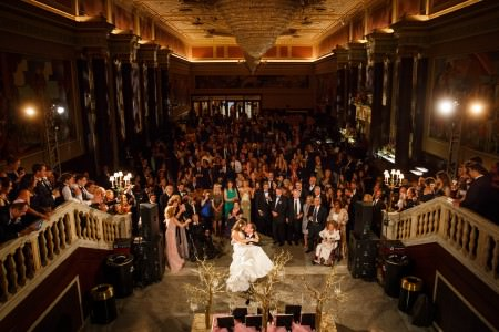 A photo looking down at a groom holding his bride in his lap while sitting on a chair in the lower center in the middle of a stage lined with steps on either side that has wedding guests standing all along the steps and down all crowded on the floor of the grand room looking back toward the camera and the wedding couple at the State Theatre that has darker walls with pillars that lead to a lighted frayed ceiling that is painted orange.