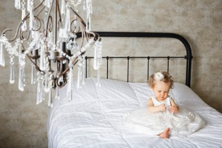 A picture of a baby girl where a white puffy dress holding a white pearl necklace sitting in the right of the photo on a black wrought iron bed covered in a white bedspread set up against a tan wall with a white pattern on and an out of focus crystal chandelier hanging from the top left of the photo in the photography studio of Genevieve Nisly Photography in Ohio.
