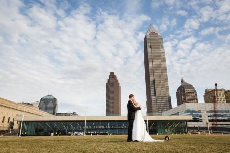 A picture of a bride and groom facing each other and hugging with the bride resting her head on the groom's shoulder outside on the green lawn standing just to the right of the center of the photo in front of the Cleveland Convention center with this glass wall and tan stone building under a blue sky full of white puffy clouds and a few brick and window tall rise buildings towards the right background of the photo.