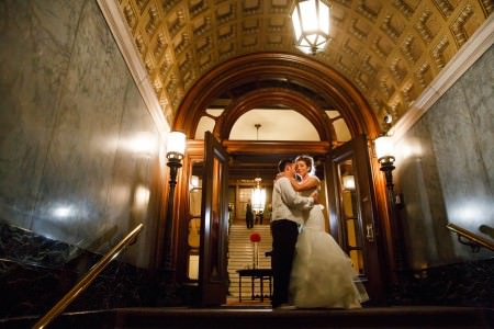 An image of a bride in her white gown hugging cheek to cheek with her groom in his black suit pants and white vest and shirt at the top of the steps just in front of an arched wooden framed door in an arched ceilinged hallway of the Union Club with grey marbled walls and golden colored tin punch ceiling.